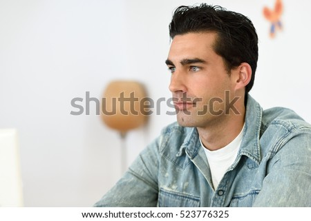 Good looking man wearing denim shirt sitting in a coffee bar. Blue eyes guy with casual clothes.