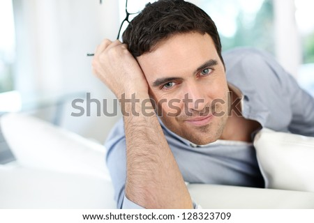 Good-looking man with eyeglasses sitting on sofa - stock photo