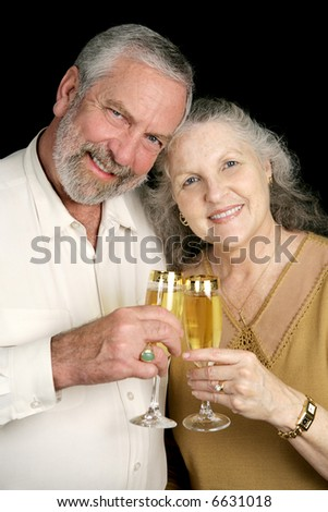 Good looking mature couple toasting the season with champagne.  Black background.