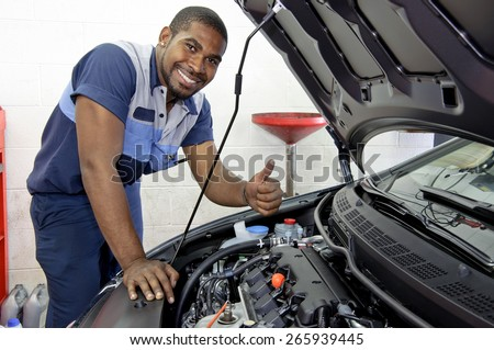 Good Looking Mechanic Checking Engine And Giving A Thumbs Up And Smiling - stock photo