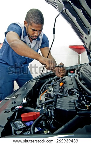 Good Looking Mechanic Working On Car Engine - stock photo