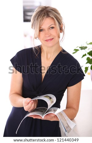 Good looking mid aged blonde reading magazine at home - stock photo