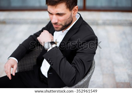 Good looking middle age man in black suit sitting outdoor  - stock photo
