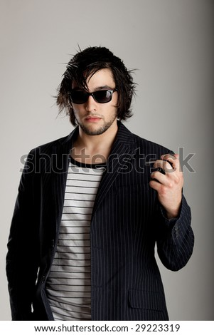 Good looking modern young man wearing a sunglasses and using a cellphone - stock photo