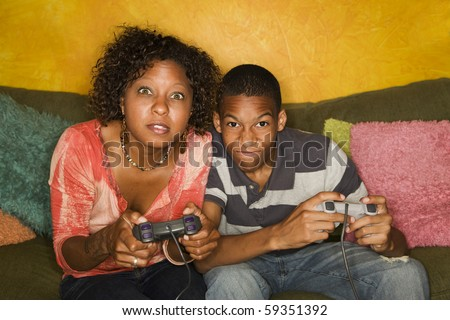 Good-looking mom and son Playing a Video Game with Handheld Controllers - stock photo