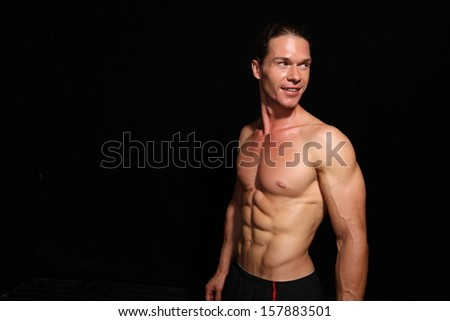 Good looking muscular athlete posing on a black background with copy space
