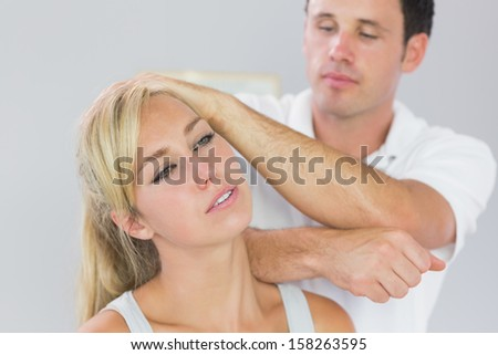 Good looking physiotherapist massaging patients neck with elbow in bright office
