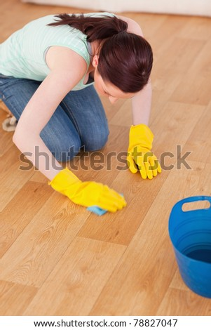 Good looking red-haired woman cleaning the floor while kneeling at home - stock photo