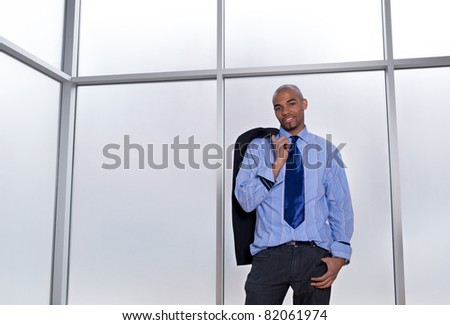 Good-looking relaxed businessman standing beside a big office window.