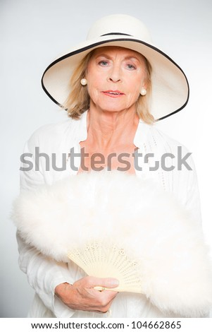 Good looking senior blond woman isolated on white background. Dressed in white and wearing white summer hat. Expression and emotion. Studio shot.