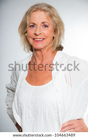 Good looking senior blond woman isolated on white background. Dressed in white. Expression and emotion. Studio shot.