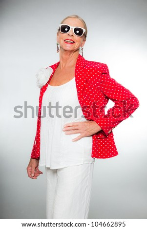 Good looking senior blond woman isolated on white background. Wearing colorful red jacket with white dots and white shirt. Wearing white sunglasses. Expression and emotion. Studio shot.