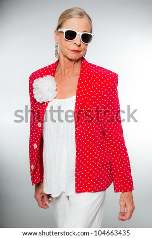 Good looking senior blond woman isolated on white background. Wearing colorful red jacket with white dots and white shirt. Wearing white sunglasses. Expression and emotion. Studio shot. - stock photo