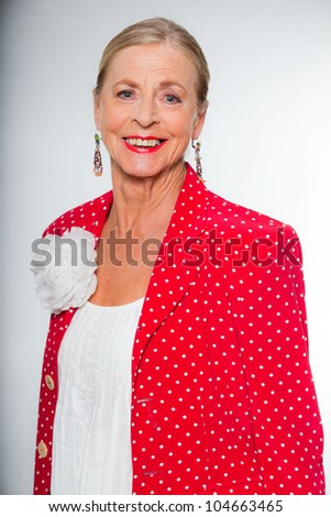 Good looking senior blond woman isolated on white background. Wearing colorful red jacket with white dots and white shirt. Expression and emotion. Studio shot.