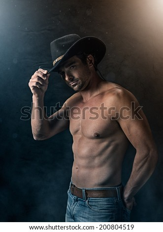 Good looking sexy cowboy without a shirt with dramatic lighting - stock photo