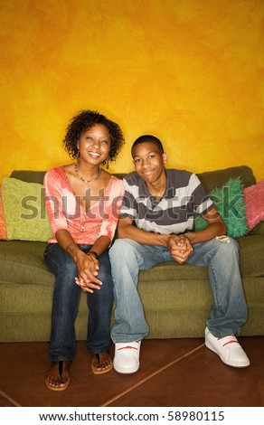 Good-looking single-parent mom and son sitting on sofa