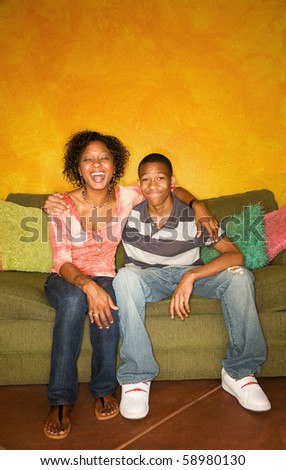 Good-looking single-parent mom and son sitting on sofa laughing - stock photo
