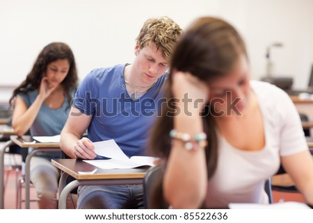 Good looking students doing an assignment in a classroom - stock photo