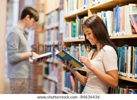 Good looking students reading books in a library