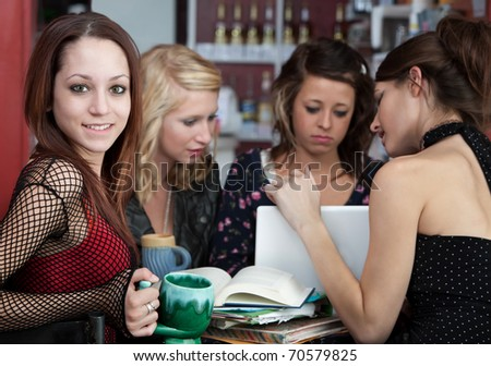Good looking teenaged girl doing homework with friends