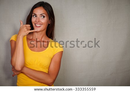 Good-looking woman gesturing a call while smiling - grey texture background - stock photo
