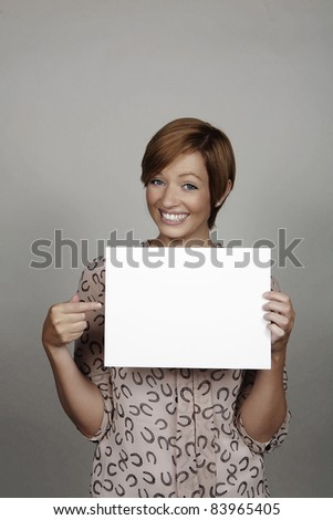 good looking woman holding a white card - stock photo