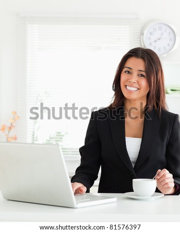 Good looking woman in suit enjoying a cup of coffee while relaxing with her laptop in the kitchen - stock photo