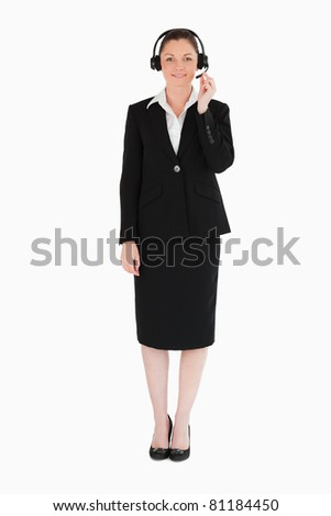 Good looking woman in suit using headphones and posing while standing against a white background - stock photo
