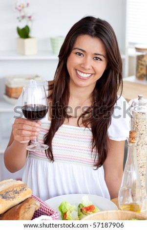 Good-looking woman sitting on sofa and drinking a glass of red wine - stock photo