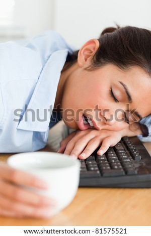 Good looking woman sleeping on a keyboard while holding a cup of coffee at the office - stock photo