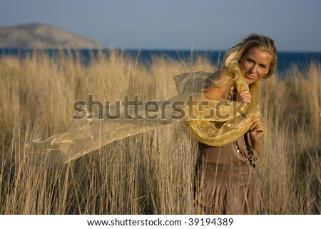 Good looking young blonde model girl with long hair standing in the autumn beads field with transparent shawl in hands