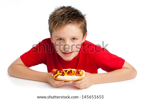Good looking young boy eating a hotdog with tomato ketchup and mustard. Isolated on white background. - stock photo