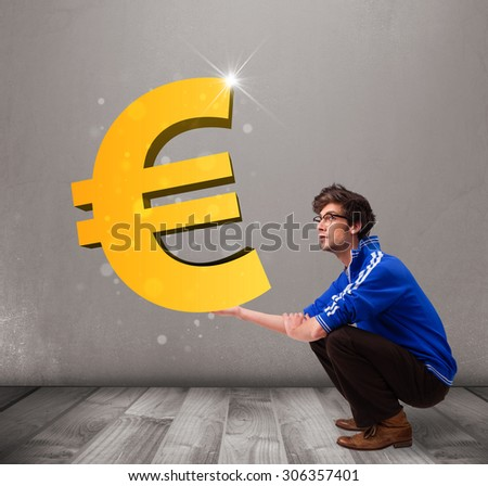 Good-looking young boy holding a big 3d gold euro sign - stock photo
