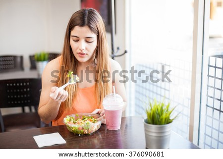 Good looking young brunette eating a salad and a smoothie by herself in a restaurant - stock photo