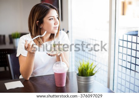 Good looking young brunette enjoying a salad and a smoothie while looking out the window in a restaurant - stock photo