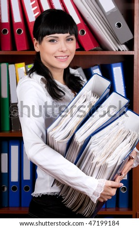 Good looking young brunette overloaded with files - stock photo