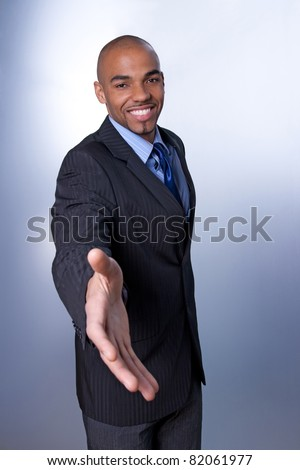Good-looking young businessman giving hand and smiling.