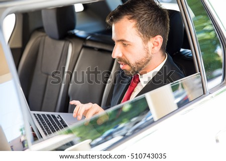 Good looking young businessman with a beard using a laptop computer to get some work done while traveling by car