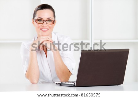 good looking young businesswoman sitting in office with laptop - stock photo