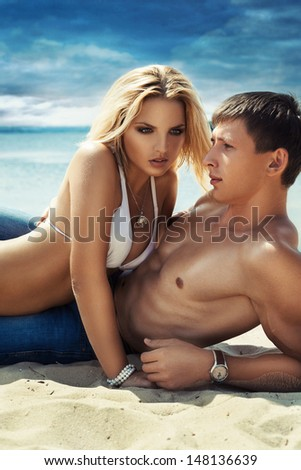 Good looking young couple lying down on the beach. - stock photo