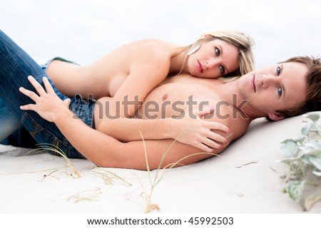 Good looking young couple lying down topless on the beach.