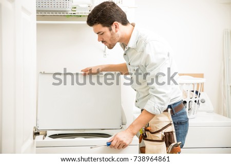 Good looking young handyman inspecting and repairing a washing machine in a laundry room