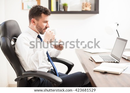 Good looking young Hispanic businessman drinking a cup of coffee while reading the news on his laptop computer - stock photo
