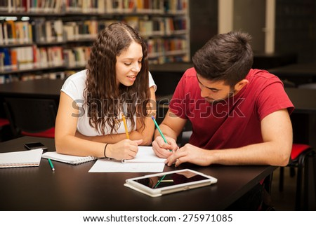 Good looking young Hispanic couple studying together in the library - stock photo