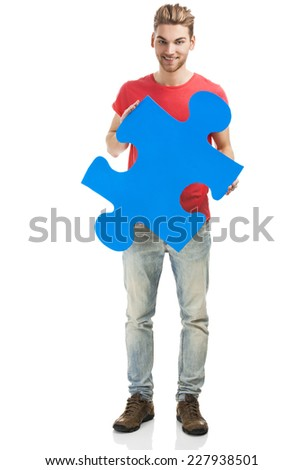 Good looking young man holding a blue puzzle piece, isolated on a white background - stock photo