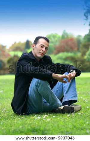 Good looking young man in black coat and denim jeans sitting in a grassy field. - stock photo