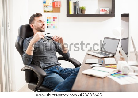 Good looking young man leaning back on his chair and taking a break from work at the office