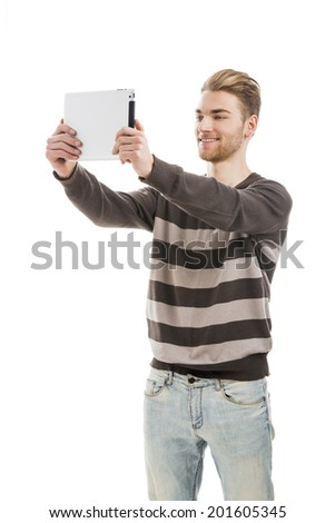 Good looking young man taking a selfie with a tablet - stock photo