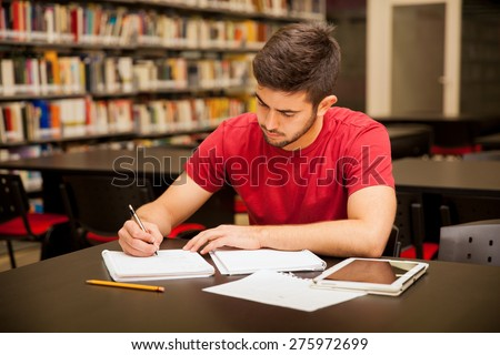 Good looking young man taking some notes and doing school work in a library - stock photo