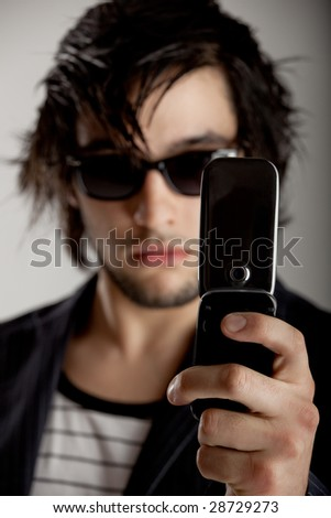 Good looking young man wearing a sunglasses and taking a picture with the cellphone - stock photo